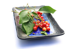 Cerezas frescas en una placa Fotografía de archivo