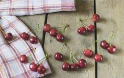 Cerezas frescas en viejo, rústico fondo de madera Fotografía de archivo libre de regalías