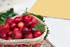 Cerezas frescas y fresas maduras rojas en una placa blanca fotos de archivo
