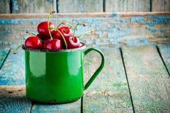 Cerezas jugosas maduras en la taza vieja Foto de archivo