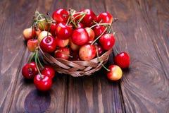Cerezas maduras en la tabla de madera en una cesta Imagen de archivo libre de regalías