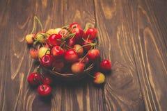Cerezas maduras en la tabla de madera en una cesta en colores en colores pastel Imagen de archivo libre de regalías