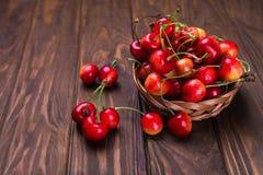 Cerezas maduras en la tabla de madera en una cesta en la vista correcta Fotografía de archivo libre de regalías