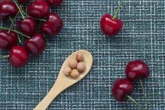 Cerezas maduras en un fondo de mimbre y una cuchara de madera de debajo con los corazones de las bayas, tres bayas por separado a imagen de archivo libre de regalías