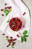 Cerezas maduras frescas en el cuenco en la tabla gris texturizada Imagenes de archivo