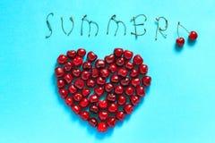 Cerezas rojas de la baya en la forma del VERANO del corazón y del texto, aún vida Foto de archivo libre de regalías