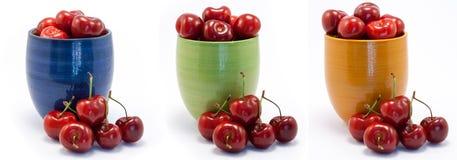 Cerezas rojas de rubíes jugosas en tazas coloreadas Fotografía de archivo libre de regalías