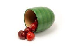 Cerezas rojas de rubíes jugosas en una taza verde Fotos de archivo