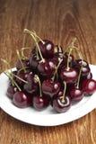 Cerezas rojas en el plato blanco Fotos de archivo