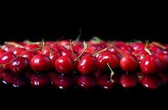 Cerezas rojas en fondo negro Fotos de archivo libres de regalías