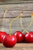 Cerezas rojas en la madera del granero Foto de archivo