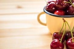 Cerezas rojas en la taza amarilla y en la tabla de madera Fotografía de archivo libre de regalías
