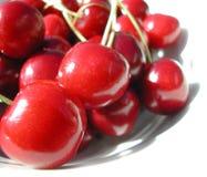 Cerezas rojas en una placa Fotografía de archivo libre de regalías