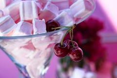 Cerezas rojo oscuro que cuelgan sobre un vidrio Fotografía de archivo