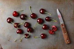 Cerezas y cuchillo Imagen de archivo libre de regalías