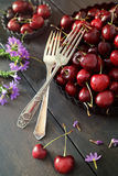 Cerezas y flores en la tabla de madera vieja Foto de archivo