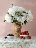 Cerezas y fresas maduras con el ramo de peonías Fotografía de archivo libre de regalías