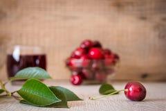 Cerezas y jugo de la cereza en la tabla Foto de archivo libre de regalías