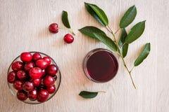 Cerezas y jugo de la cereza en la tabla Fotografía de archivo libre de regalías