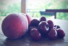 Cerezas y melocotones rojos maduros en la tabla de madera, retro filtrado Imagen de archivo libre de regalías