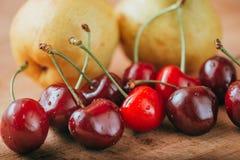 Cerezas y pera, frutas frescas en la tabla de madera Imagen de archivo