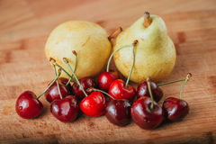 Cerezas y pera, frutas frescas en la tabla de madera Imágenes de archivo libres de regalías