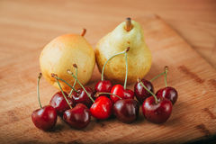 Cerezas y pera, frutas frescas en la tabla de madera Foto de archivo