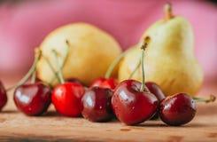 Cerezas y pera, frutas frescas en la tabla de madera Imagen de archivo libre de regalías