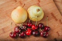 Cerezas y pera, frutas frescas en la tabla de madera Fotos de archivo libres de regalías