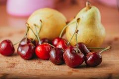 Cerezas y pera, frutas frescas en la tabla de madera Fotografía de archivo