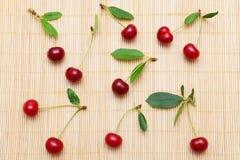 Cerezas y tallos rojos fotografía de archivo