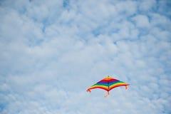 Cerf-volant coloré volant sur le fond nuageux de ciel bleu Photos libres de droits