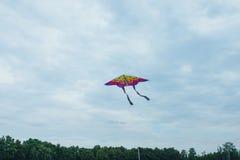 Cerf-volant coloré volant du ` s d'enfants, ciel foncé avec des nuages Photos stock
