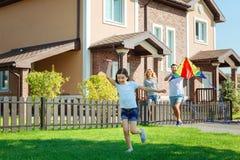 Cerf-volant gai de vol de fille avec des parents dans l'arrière-cour Photo stock