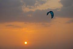 Cerf-volant surfant au coucher du soleil Image stock