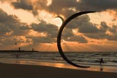 Cerf-volant surfant dans le coucher du soleil à la plage Image libre de droits