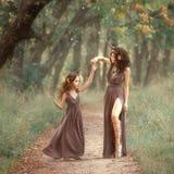 Cerfs communs féeriques de mère sur le chemin tournant sa fille sur une traînée de forêt, longues robes brunes de port, montrant  photographie stock