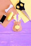 Cerfs communs mignons de Noël faits de feutre Morceaux jaunes et bruns de feutre, fil, aiguille, ciseaux sur le fond en bois lila Photographie stock