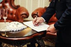 Cerimónia de casamento Equipe o contrato de união de assinatura, close up, noivo s fotos de stock royalty free