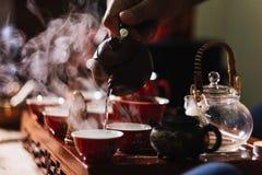 Cerimónia de chá O homem derrama a água quente do bule no copo de chá chinês vermelho imagens de stock royalty free