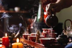 Cerimónia de chá O homem derrama a água quente no copo de chá chinês imagem de stock royalty free