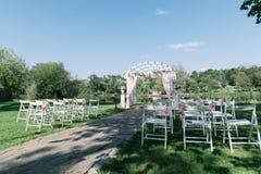 Cerimônia de casamento bonita do verão fora Suporte decorado das cadeiras na grama Arco do casamento feito do pano claro e o bran Foto de Stock