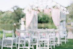 Cerimônia de casamento bonita do verão fora Suporte decorado das cadeiras na grama Arco do casamento feito do pano claro e o bran Fotos de Stock Royalty Free