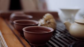 A cerimônia de chá chinesa, na tabela é três copos, eles derramou de um puer da chaleira Close-up filme