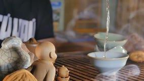 A cerimônia de chá do chinês tradicional e derrama o chá em um vidro da argila Chá de derramamento com a ajuda da concha foto de stock royalty free