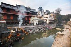 Cerimônia da cremação ao longo do rio santamente de Bagmati em Bhasmeshvar Ghat no templo de Pashupatinath Fotos de Stock Royalty Free