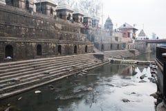 Cerimônia da cremação ao longo do rio santamente de Bagmati em Bhasmeshvar Ghat no templo de Pashupatinath Imagem de Stock