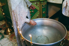 Cerimonia battesimale La bibbia della chiesa dell'altare esamina in controluce l'icona trasversale della corona Fotografia Stock Libera da Diritti