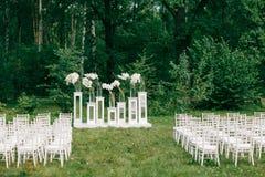 Cerimonia di cerimonia nuziale in un bello giardino sedie bianche e tavole rispecchiate Vaso di vetro con l'amarillide delle call immagine stock