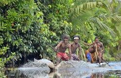Cerimonia di guerra della canoa della gente di Asmat Cacciare teste di una tribù di Asmat in una maschera con una o Fotografia Stock